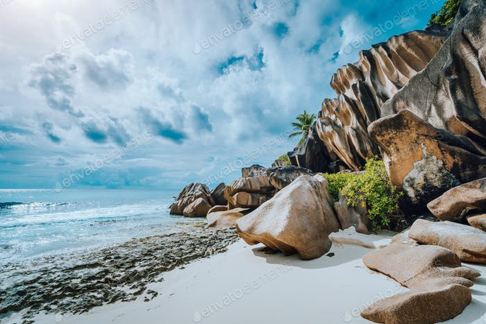 Picturesque granite boulders formation on tropical white sand beach Grand Anse, La Digue island