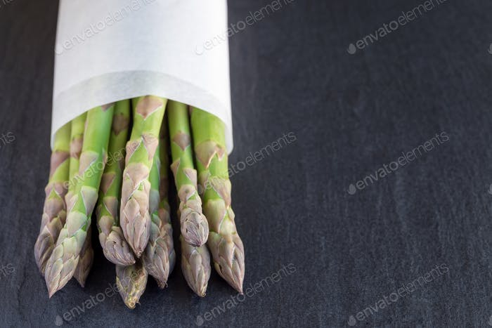 Bunch of fresh green asparagus on dark slate background with cop