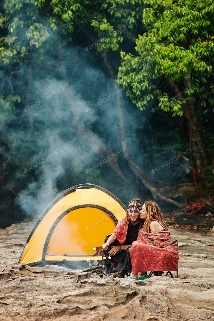 Couple making smores when camping in forest
