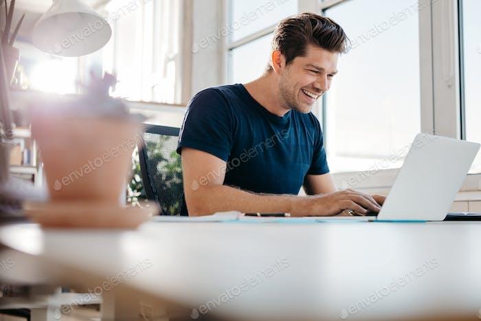 Glückliche junge Geschäftsmann mit Laptop an seinem Schreibtisch im Büro