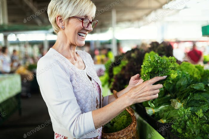 Only the best fruits and vegetables. Beautiful mature woman buying fresh food on market