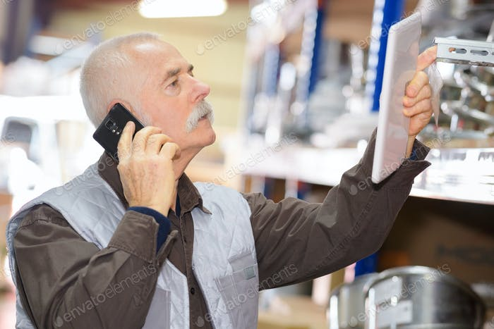 Senior man in stores with cellphone and tablet