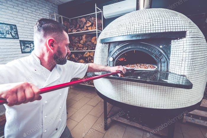Hombre barbudo chef preparando pizza en el Negocios local