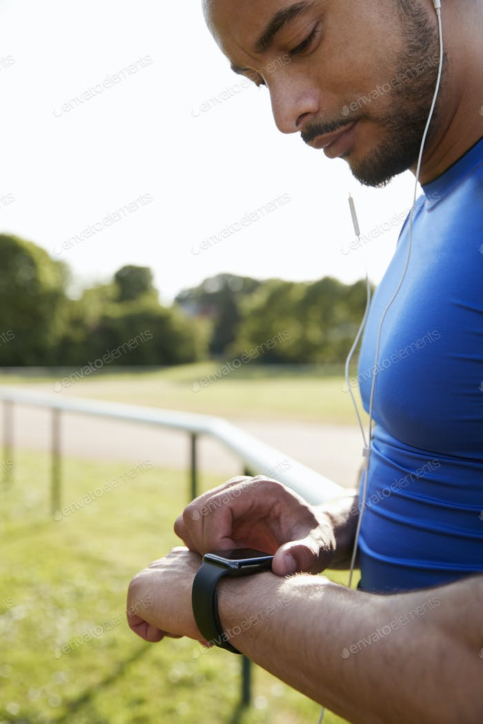 Male athlete at running track setting smartwatch app