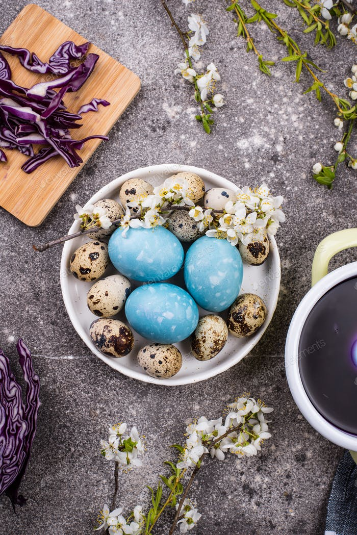 Process of painting Easter eggs in blue