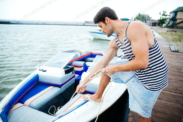 Young handsome man preparing boat to start a journey