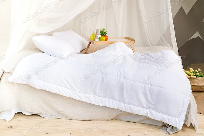 a cozy bedroom in pastel colors with a wooden floor, a large four-poster bed, tray with fruit and a