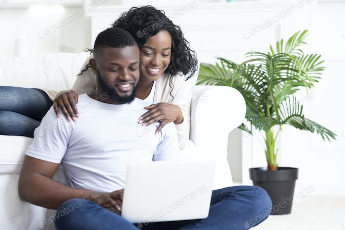 Happy young african american couple using portable pc at home