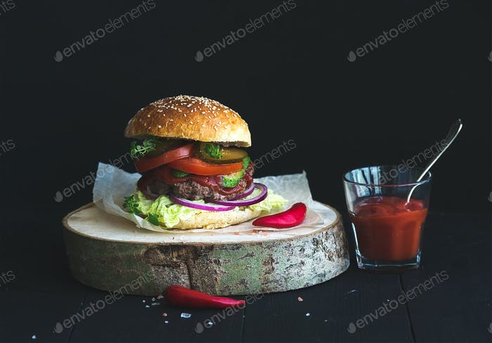 Fresh homemade burger on wooden serving board with spicy tomato sauce