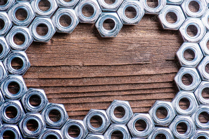 Chrome nuts on wooden background
