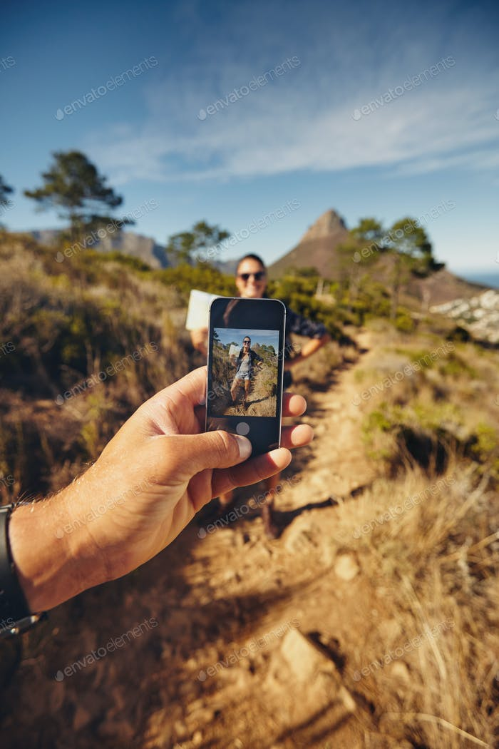 Man talking pictures of a woman with mobile phone - Hiking trip