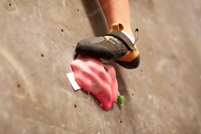 Fuß der Frau auf Indoor-Kletterhalle Wand halten