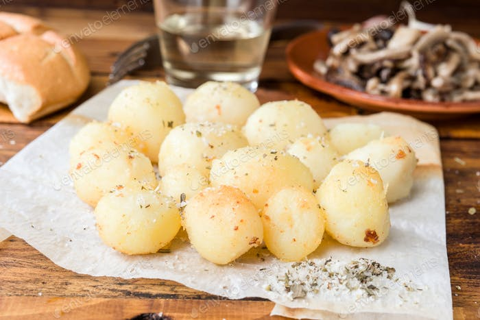 Roasted potatoes with aromatic salt on wood in baking paper