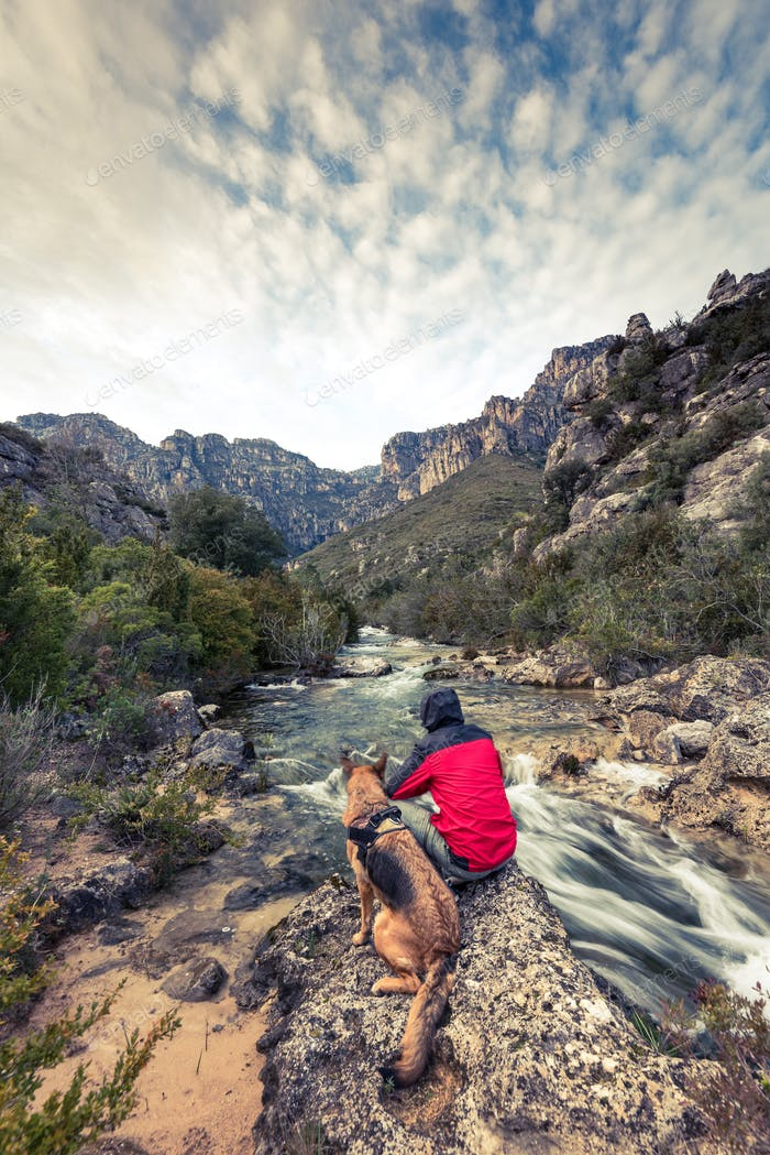 Wanderlust man and dog in wild mountains by the river