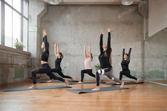 Group of fitnesswomen stretching on mats