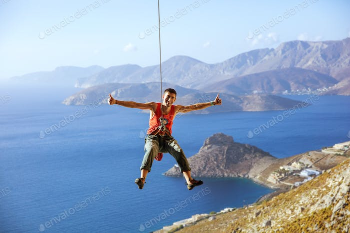 Rock climber swinging on rope and showing thumbs up