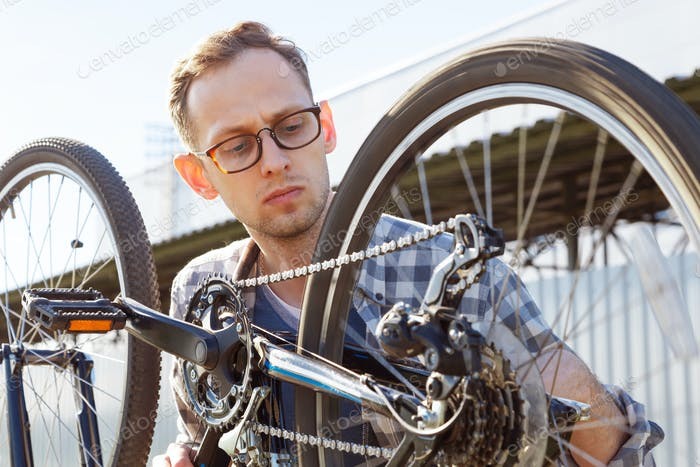 The mechanic man checks transmission system of the bicycle outdoor.