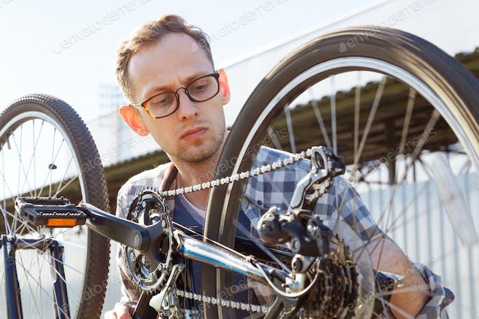 Der Mechaniker überprüft das Übertragungssystem des Fahrrads im Freien.