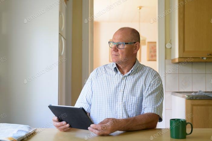 Senior sitzt in der Küche und denkt
