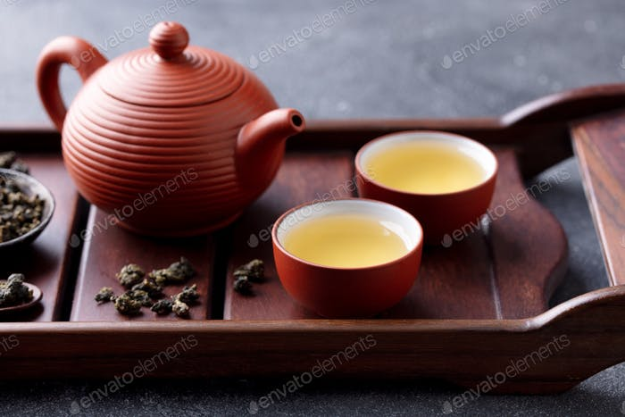 Grüner Tee Oolong in Teekanne und Chawan Schalen, Becher auf einem Holztablett. Grauer Hintergrund. Nahaufnahme.