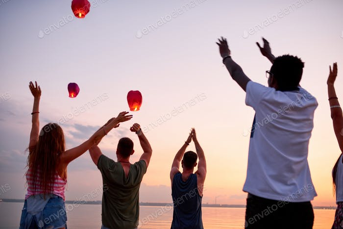 Excited young people saying goodbye to flying sky lanterns