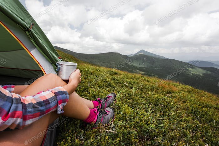 Girl sitting in they tent with hot tea