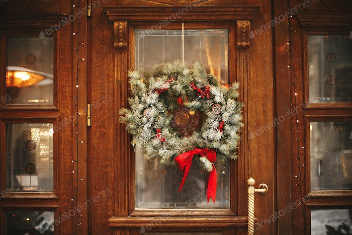 Stylish christmas wreath with red bow and berries at front doors