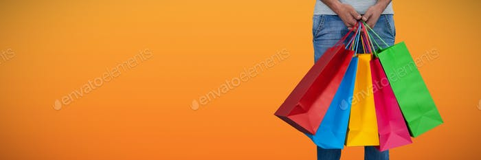 Composite image of low section of man carrying colorful shopping bag standing against white backgrou