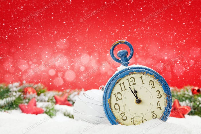 Christmas greeting card with alarm clock and decor in snow