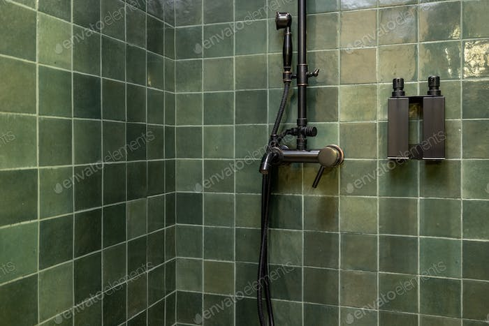 Green square bathroom tile and shower plumbing