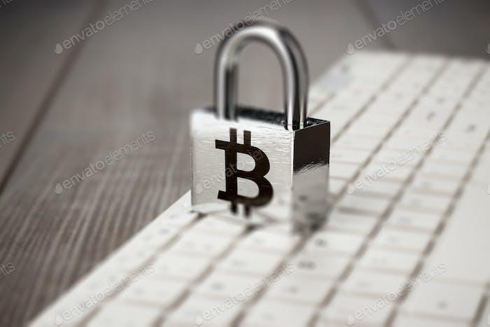 Vorhängeschloss mit Bitcoin Symbol auf weißer Computertastatur