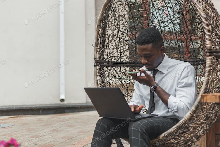 Business african american man holding smartphone, dictating voice message