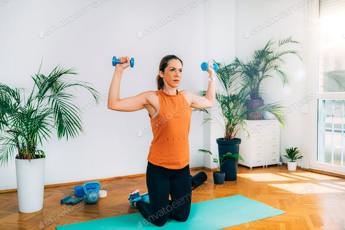 Woman exercising with Dumbbells. Shoulder Press Exercise.