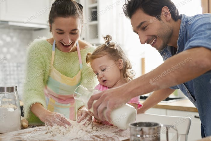 Daughter helping parents with cooking