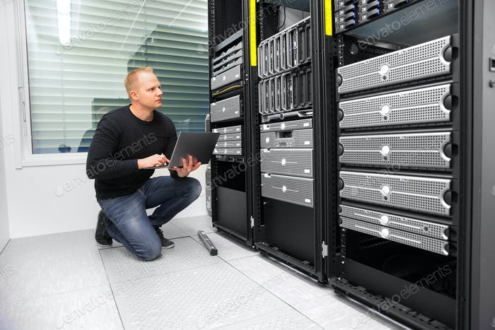 Consultant Using Laptop While Monitoring Servers In Datacenter