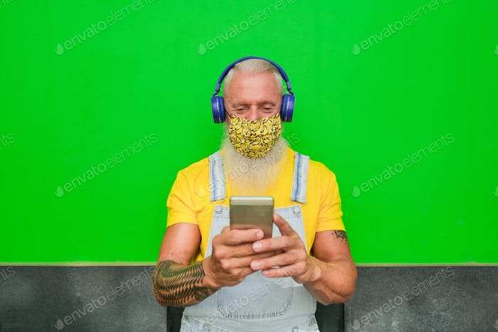 Elderly hipster man enjoy technology and wearing protective face mask