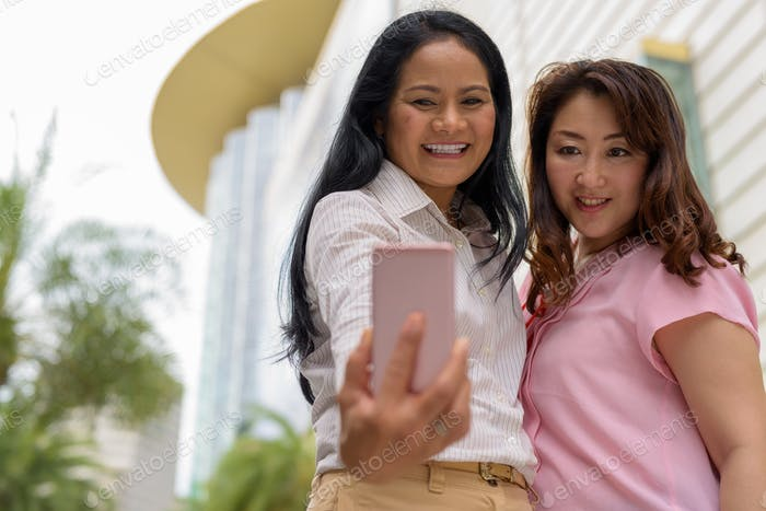 Two mature Asian women together outside the mall in Bangkok city