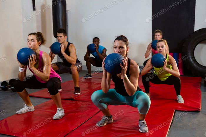 Young athletes crouching with exercise balls
