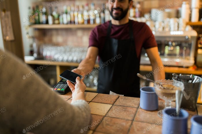 man with payment terminal and hand with smartphone