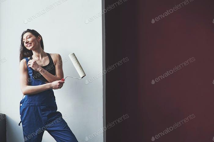 Spezielle Ausrüstung benötigt. Junge Hausfrau beschloss, Tapeten in ihr neues Haus im Zimmer  zu kleben