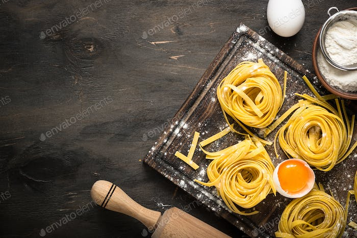 Prepartion homemade pasta tagliatelle at wooden table.