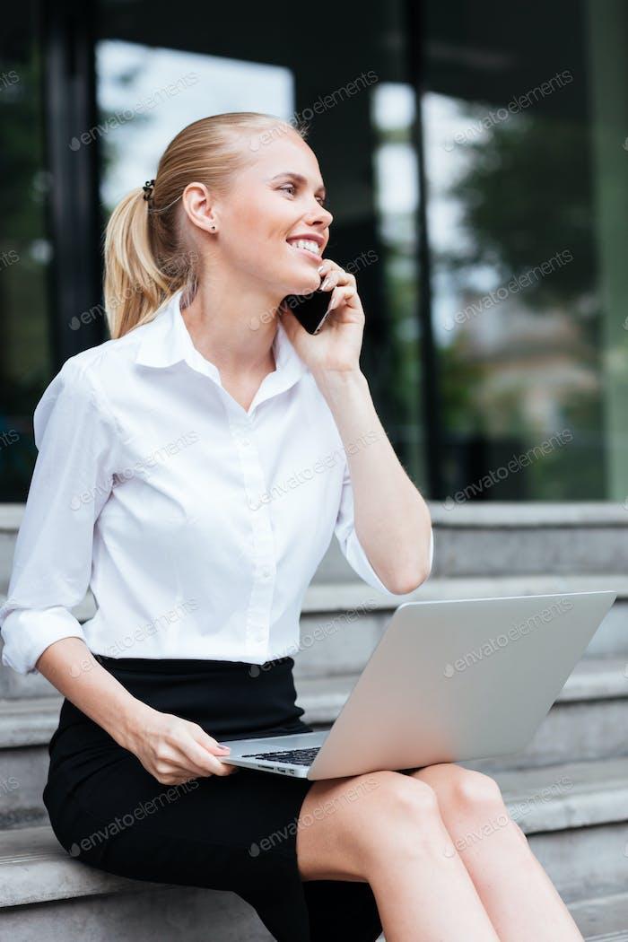 Mujer de negocios con Ordenador portátil y teléfono sentado en las escaleras