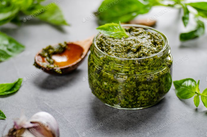 Glass jar with genovese pesto sauce on stone table with basil leaves and garlic aside