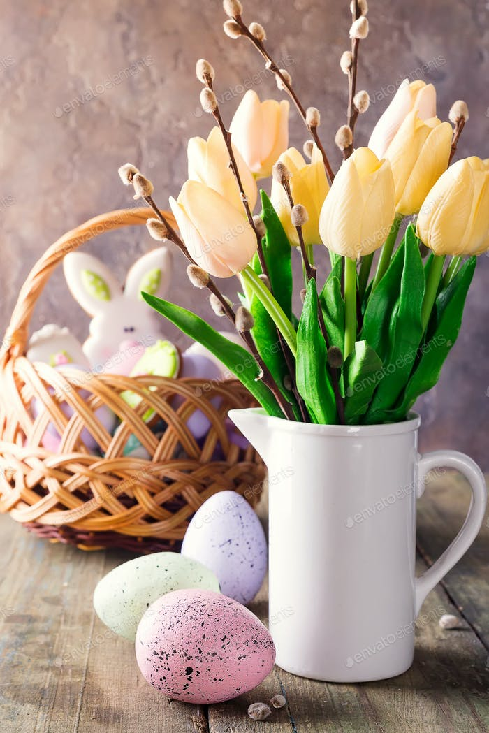 Yellow tulips in a vase and easter colorful eggs on a wooden table. Gift and Easter eggs