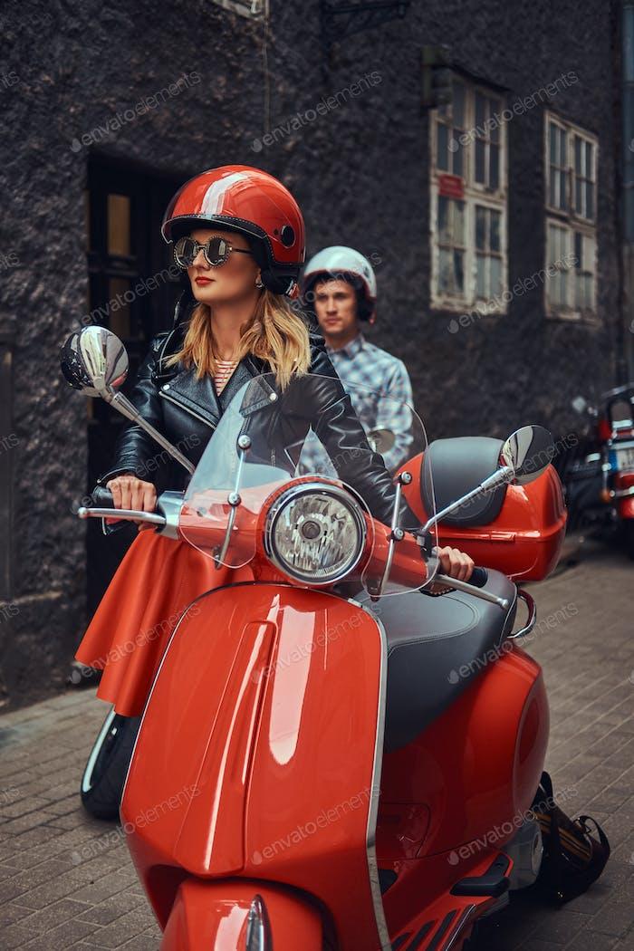Schöner Mann und ein sexy stilvolles Mädchen sind mit Retro-italienischen Roller zu Fuß