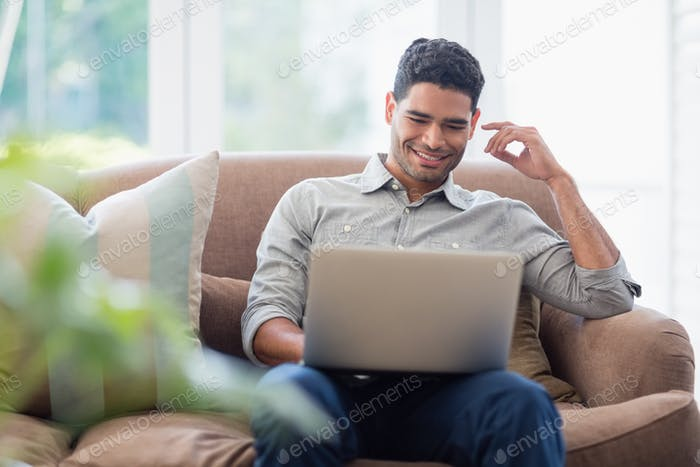 Man sitting on sofa and using laptop in living room