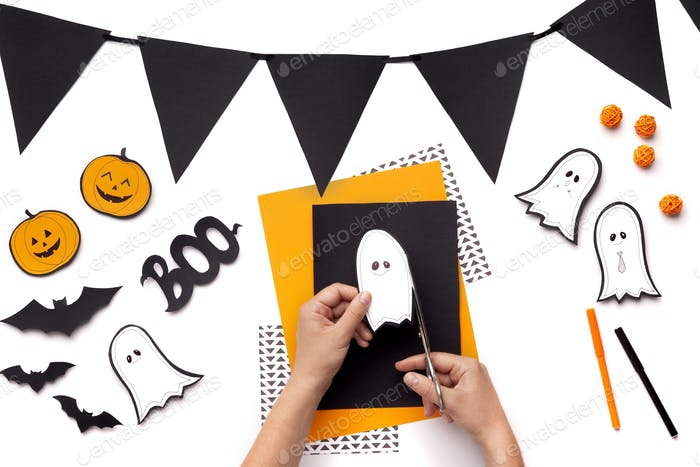 Woman cutting out cute ghosts and pumpkins on background