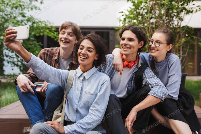 Group of cheerful students sitting and taking cute photos on cellphone while spending time together