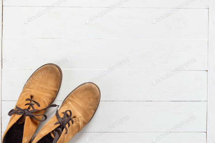 Pair of new nubuck boots on white wooden background. Top view