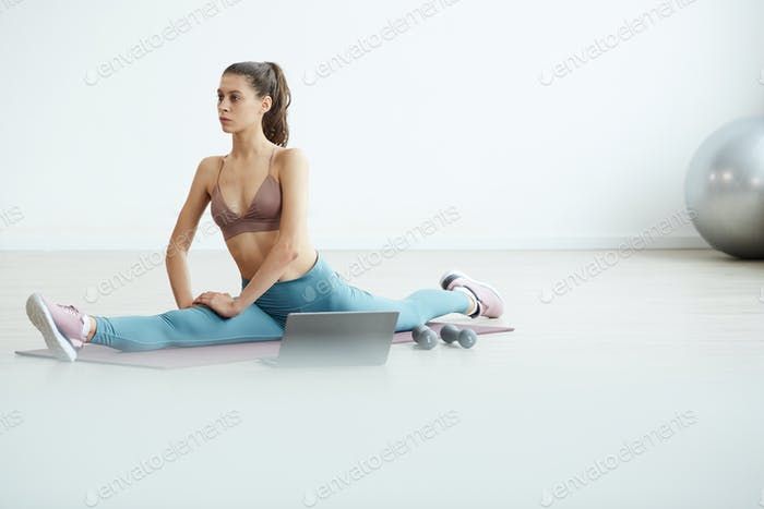 Contemporary Woman Stretching in White Room